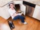 Young woman (20s) doing home repairs, fixing leak under kitchen sink.